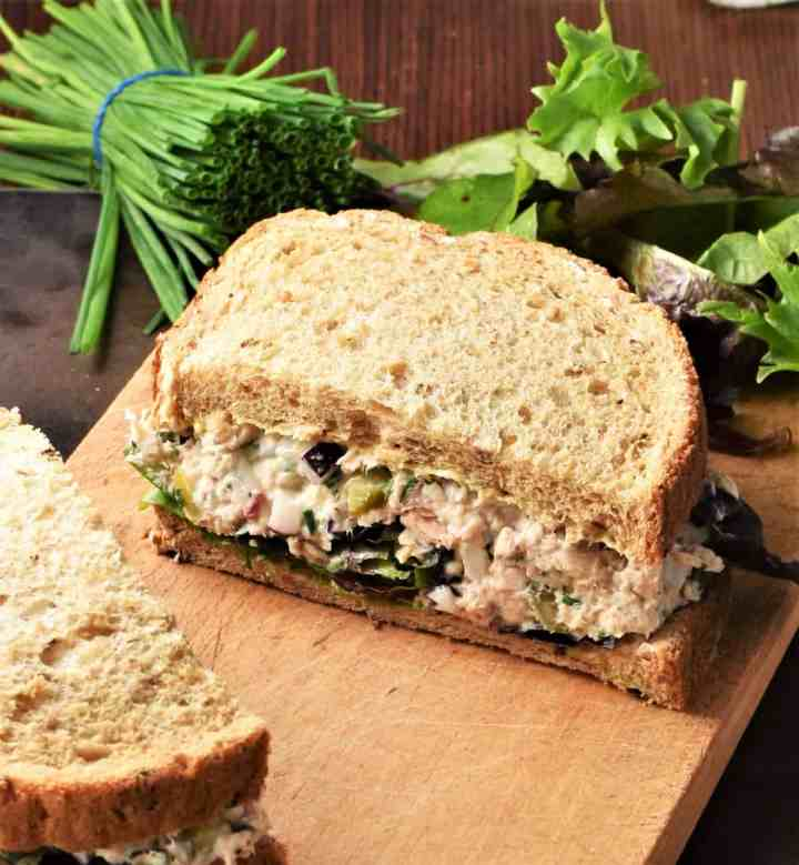 Side view of salmon salad sandwich with herbs in background.
