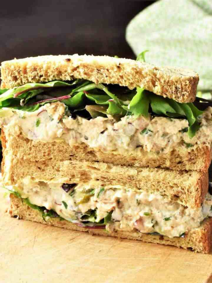 Side view of salmon salad sandwich cut in half on top of board.