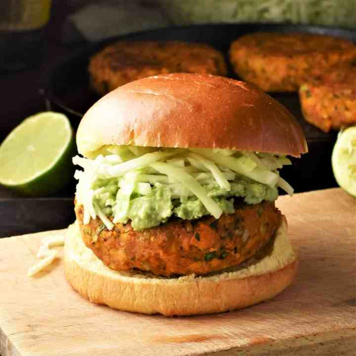Side view of sweet potato burger with cabbage on top of wooden board with lime and burgers in background.