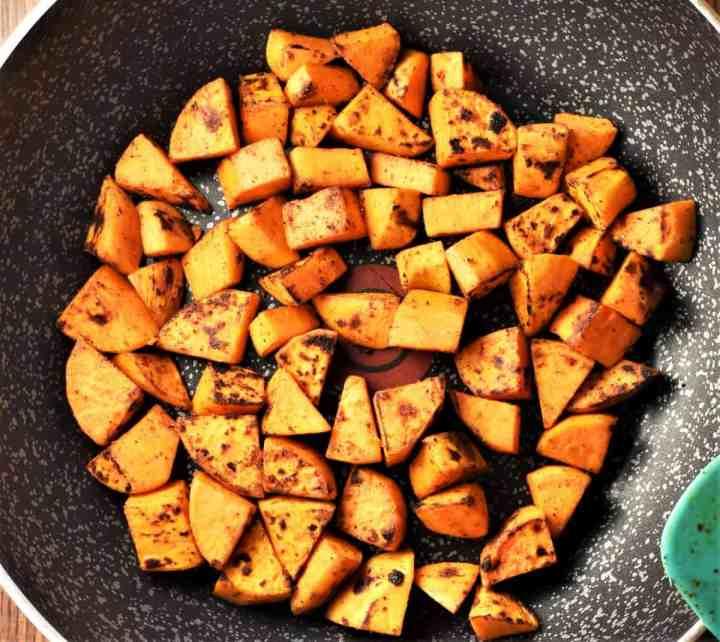 Frying sweet potato chunks in large pan.