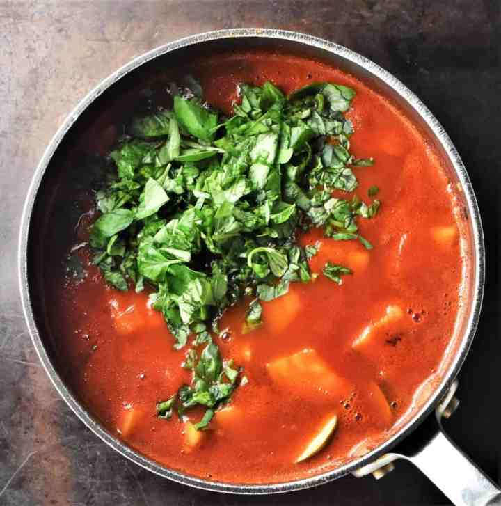 Tomato soup with chunks of zucchini and chopped basil in pot.