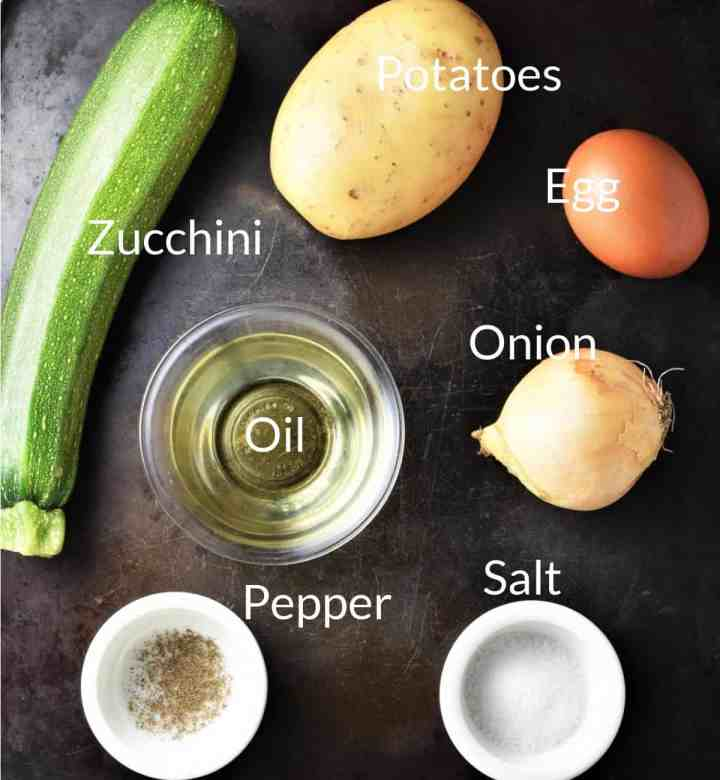 Ingredients for making potato zucchini fritters on top of dark metal surface.