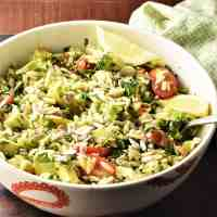 Side view of raw broccoli salad in white bowl with spoon.