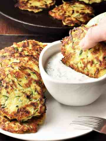 Side view of potato zucchini fritters on top of white plate with fritter dipped in yogurt dip.