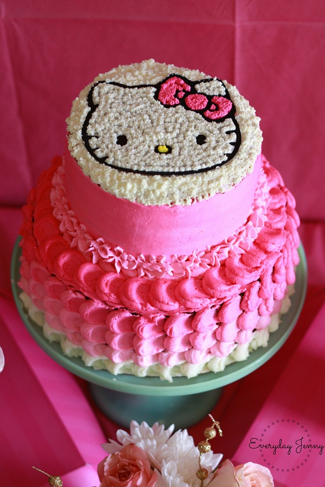 Hello Kitty Cake. Whipped cream frosting, two tier cake with ombre petals and a piped Hello Kitty