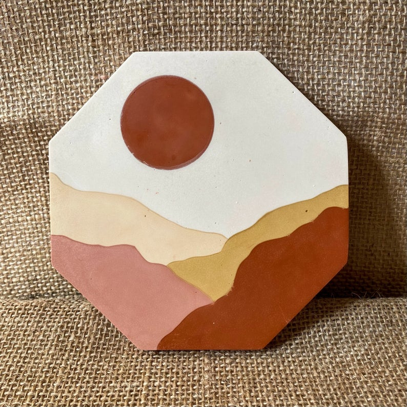 A hexagon tile resting on a piece of hessian material. The tile is white with a brown sun painted on with pink, gold and brown desert dunes painted on