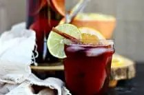 glass of fall sangria with cinnamon stick, slice of lime and orange over ice in front of linen and glass pitcher of sangria to serve