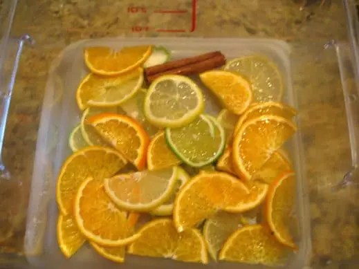 large food storage container filled with sliced lime, lemon, oranges and cinnamon for fall sangria