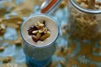 blue glass with peanut butter smoothie topped with strawberry jam and chopped peanuts