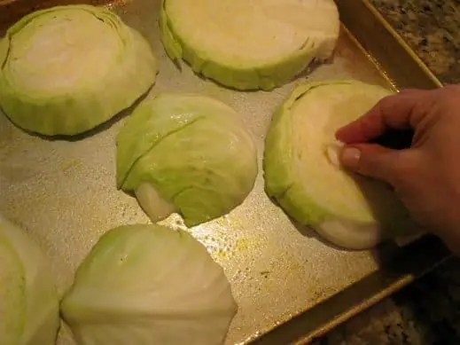 Rubbing sliced cabbage steaks with raw garlic clove on a baking sheet