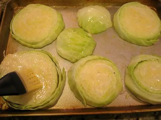 Using a silicone pastry brush to rub olive oil all over the cabbage steaks on a baking sheet