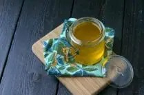 glass mason jar with liquid ghee on a blue and yellow napkin on a wood board