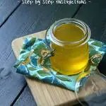 glass jar of liquid ghee on a wood cutting board with a blueish yellow napkin