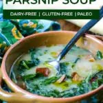ceramic bowl of parsnip soup with greens and a old looking spoon