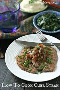 white plate with cooked cube steak topped with fried onion and parsley