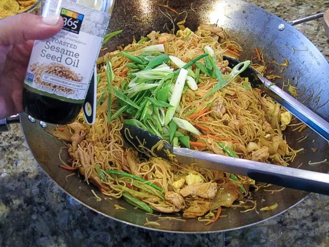 putting sesame oil and scallions on singapore rice noodles right before serving