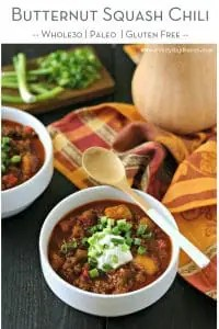 butternut squash chili in white ceramic bowl topped with sour cream and chopped scallions