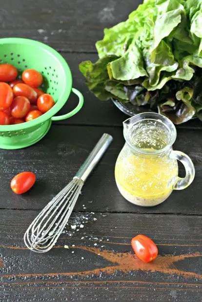garlic salad dressing in a small glass canister on a wooden board with cherry tomatoes in a green colander, a head of red leaf lettuce and a small whisk on a dark wood background