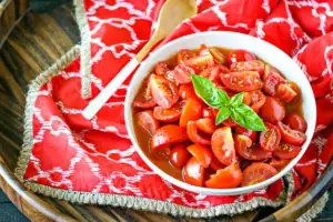 bowl of tomato salad made with jersey tomatoes with basil on top