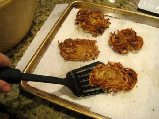 removing cooked gluten free potato latkes to a baking sheet lined with paper towels to absorb oil