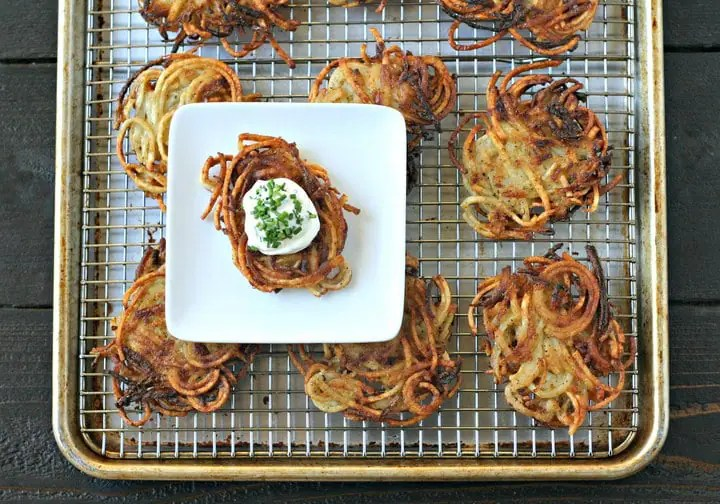 overhead view of cooked potato latkes on a cooling rack inserted on a sheet pan with a square plate featuring one latke topped with sour cream and chopped chives