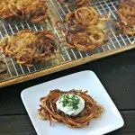 square white plate with one crispy cooked potato latke topped with sour cream and chopped chives in front of a sheet pan filled with cooked potato latkes