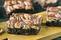 baked pecan brownies cut into squares on a wood board