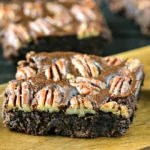 close up of pecan brownie on a wood cutting board