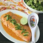 whole fillet of wild salmon in red curry sauce with lime and bowl of broccoli