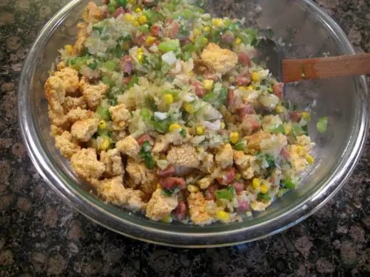 large mixing bowl with ingredients to make cornbread sausage stuffing getting mixed by a wooden spoon