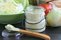 glass jar with garlic chive mayonnaise in front of lettuce