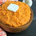wood bowl with mashed sweet potatoes made in the InstantPot. topped with vegan butter