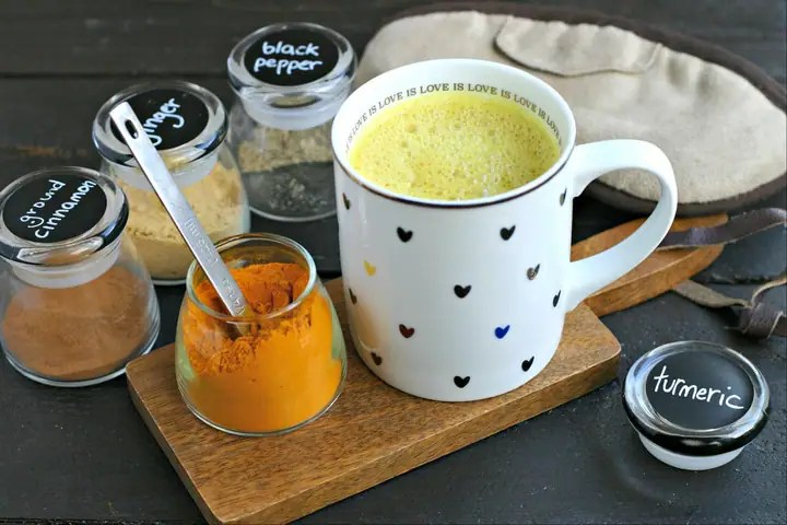 mug with golden milk (turmeric milk) on a small wood cutting board and dried spices