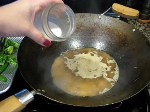 adding arrowroot mixture to sauce in wok