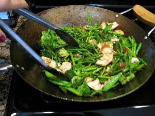 mixing chicken and vegetables with sauce in the wok