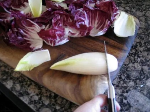 trimming the end of a head of endive on a wood cutting board