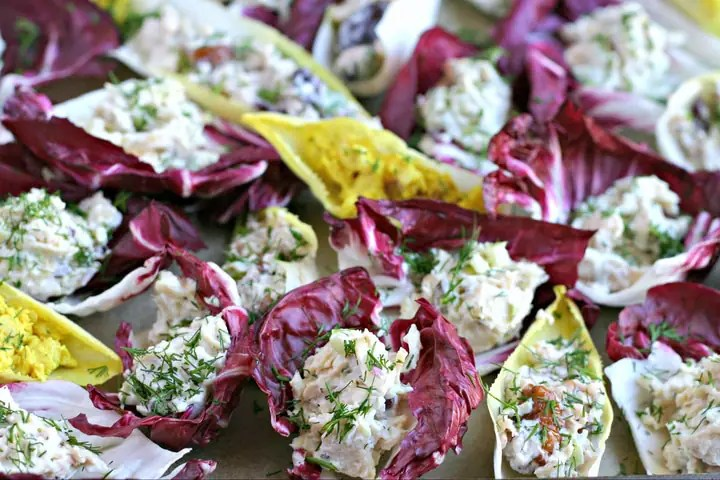a tray of endive and radicchio leaves stuffed with chicken salad and fresh dill