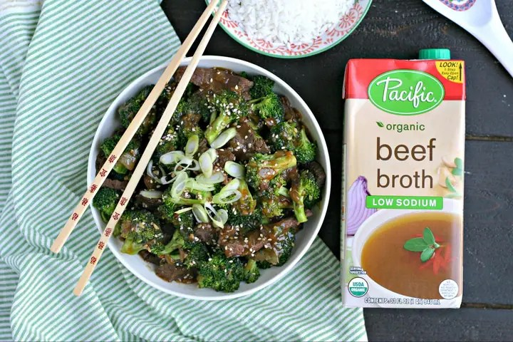 a bowl of beef and broccoli on a green and white striped linen with chopsticks, rice and a carton of beef broth