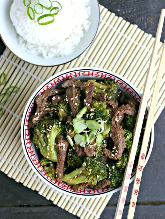 bamboo mat with bowl of beef and broccoli, chopsticks resting on bowl, small bowl of white rice with green scallions on top