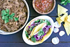 bowl of pulled pork made in the pressure cooker, tacos and salsa with sliced radish and chips