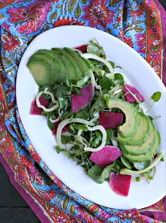 vertical image of white oval platter with colorful salad on it