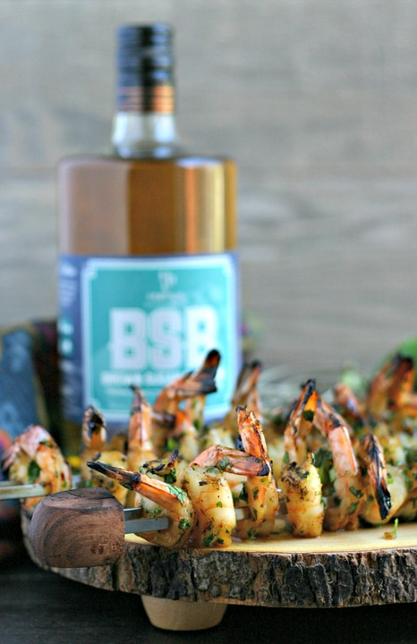 close up of grilled shrimp skewers on a wood platter with bottle of bourbon in background