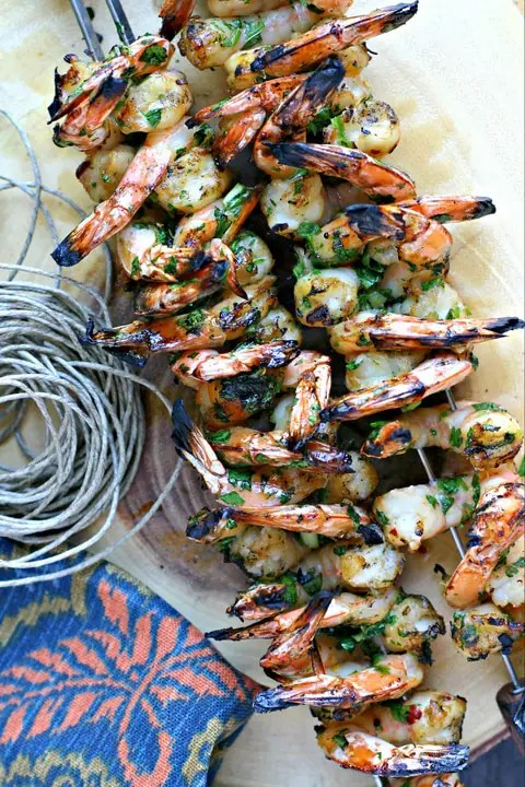 shrimp on skewers on a wood platter with piece of twine and napkin
