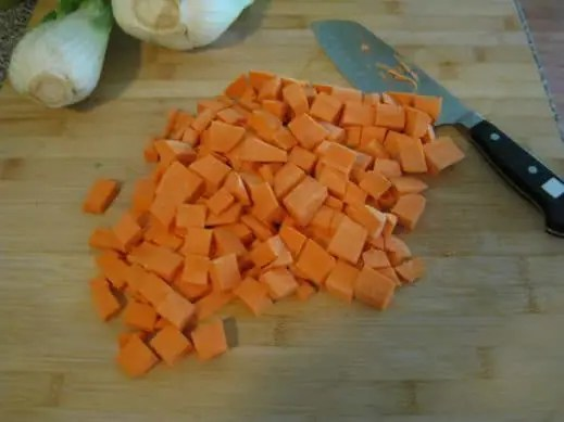 peeled and diced sweet potatoes on a wood cutting board with a sharp knife