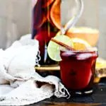 close up of red sangria with ice in front of glass pitcher