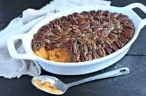 white oval casserole dish filled with healthy sweet potato casserole with pecan topping and a silver serving spoon