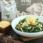 white bowl with cooked sukuma wiki topped with millet next to small square wood bowl of uncooked millet, african wood serving spoon, open bag of Bob's Red Mill millet and distressed linen in backgroun