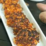 close up of cooked sweet potato laktes on a thin white rectangle serving platter