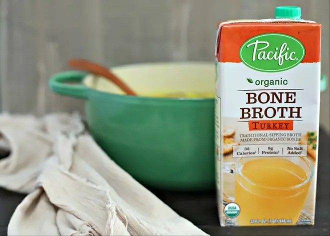 Quart of Pacific Foods Organic Turkey Bone Broth in front of green soup pot with wood ladle and beige linen