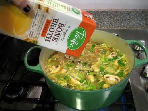 adding turkey bone broth to a large pot of vegetables to make easy turkey soup